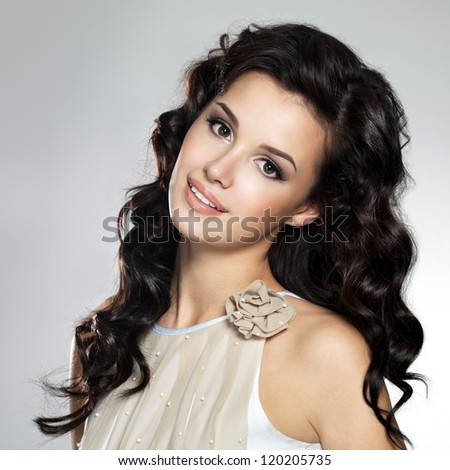 Beautiful young smiling  woman with long brown hair. Pretty model poses at studio. - stock photo