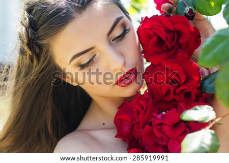 Beautiful young smiling woman with long curly hair posing near red roses in a garden - stock photo