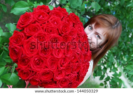 Beautiful young smiling woman with red roses - stock photo