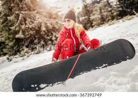 Beautiful young smiling woman with snowboard enjoying a sunny winter day.
