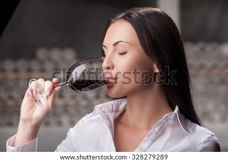 Beautiful young sommelier is drinking red wine in cellar. The woman is standing and holding wineglass. She closed eyes with pleasure - stock photo