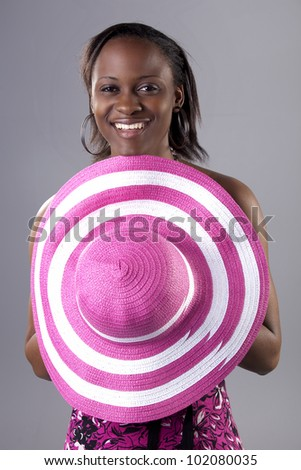Beautiful young South African woman in bright colors holding a hat. - stock photo