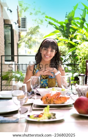 Beautiful young spanish woman smiling by the dining table, about to have a meal, outdoor home environment - stock photo