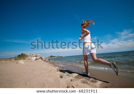 Beautiful young sport woman running in sea coast on sunny summer day - stock photo