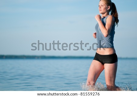 Beautiful young sport woman running in water on sunny summer day - stock photo