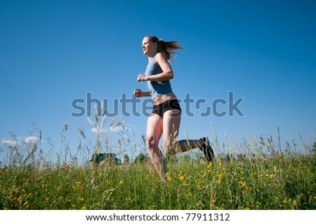 Beautiful young sport woman running over green grass on sunny summer day - stock photo