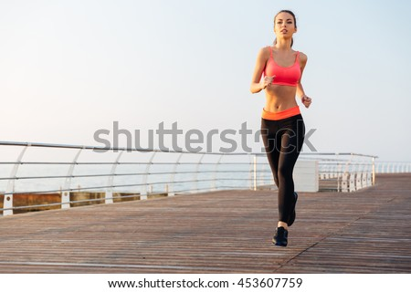 Beautiful young sportswoman training and running on pier in the morning - stock photo