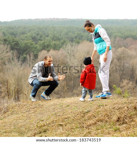 Beautiful young sporty family stands back on the mountain - stock photo