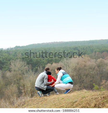 Beautiful young sporty family stands back on the mountain