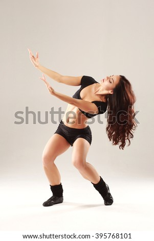 Beautiful young sporty muscular woman dancing on grey background.