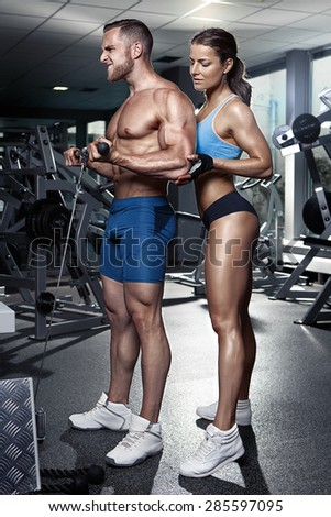 beautiful young sporty sexy couple doing biceps workout in gym - stock photo