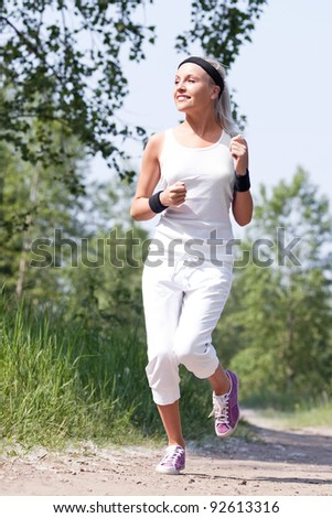beautiful young  sporty woman running in the park on a warm summer day