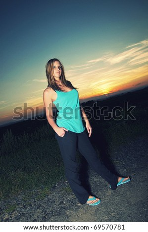 Beautiful young sporty woman standing on a road at summer sunset - stock photo