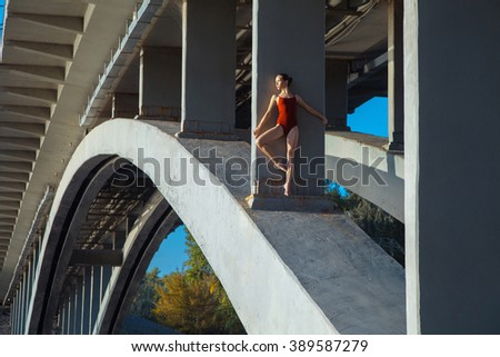 Beautiful young strong healthy woman ballerina gymnast in red leotard posing as model on bridge girder and blue sky and looking into the distance.