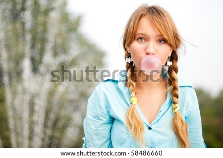 beautiful young student girl blowing bubble from chewing gum and looking into the camera - stock photo