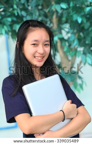 Beautiful young student girl holding labtop standing in park, smiling
