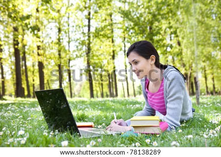 beautiful young student girl lying on grass with laptop and books, looking into the laptop and smiling - stock photo