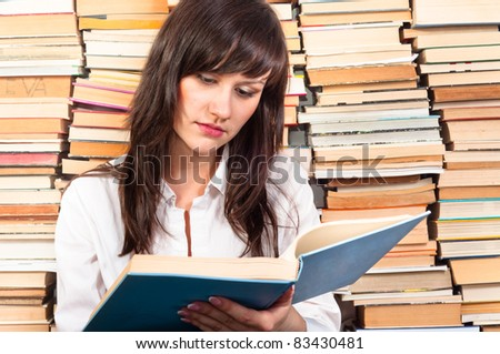 Beautiful young student girl reading from a big book - stock photo
