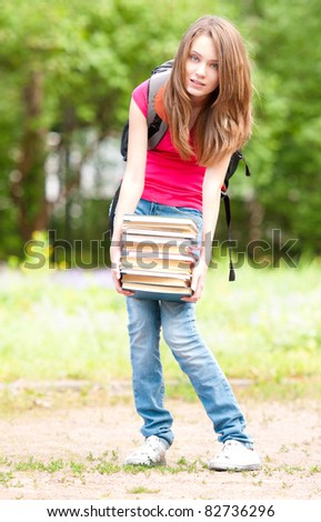 beautiful young student girl standing in park and holding pile of heavy books in her hands. Looking into the camera. Summer or spring green park in background - stock photo