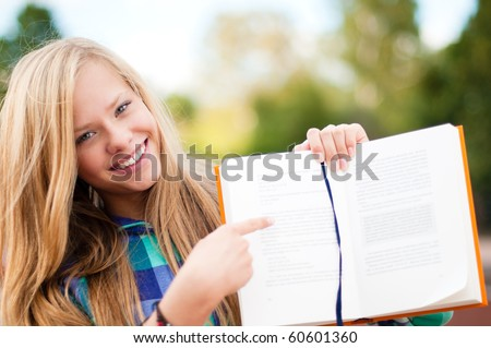 beautiful young student girl standing in park, smiling and looking into the camera, showing you something in book - stock photo