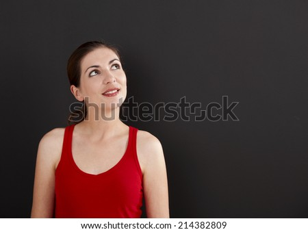 Beautiful young student smiling over a black chalkboard, with copyspace for the designer - stock photo