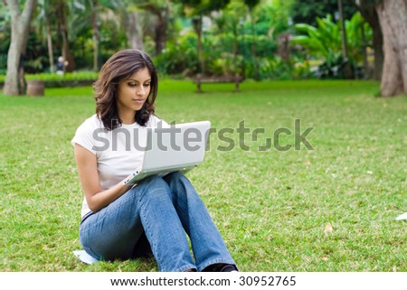 beautiful young student using laptop on grass - stock photo