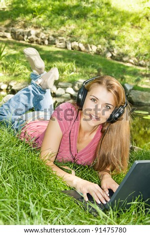 Beautiful young student with headphones using computer outdoors. - stock photo