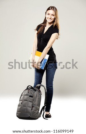 Beautiful young student with school bag and books - stock photo