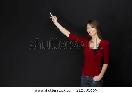 Beautiful young student writing on chalkboard with copyspace for designer - stock photo