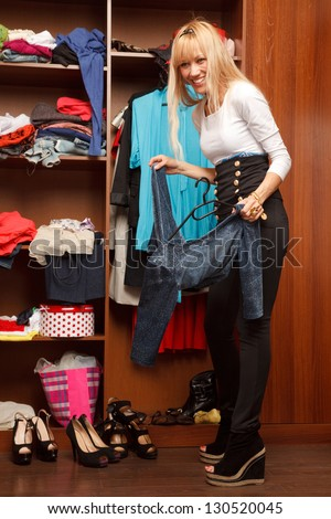 Beautiful young stylish woman stands near  wardrobe   and holding  dress