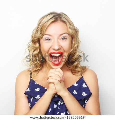 Beautiful young surprised blond woman. Studio shot. - stock photo