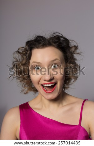 Beautiful young surprised blond woman. Studio shot. - stock photo