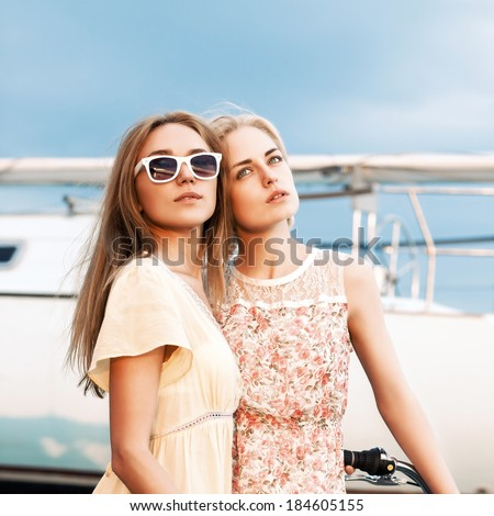 beautiful young tanned girl in summer dress hugs her blonde girlfriend sitting on cruiser bike. both look dreamily into distance - stock photo