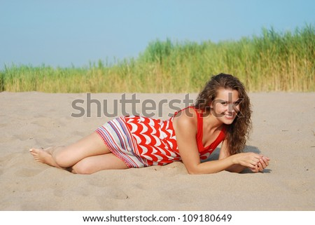 beautiful young tanned smiling girl in a bright color dress lying on the sand - stock photo