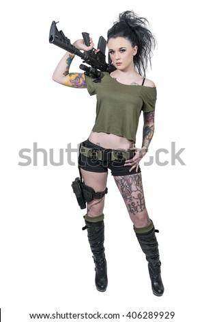 Beautiful young tattooed woman holding an automatic assault rifle - stock photo