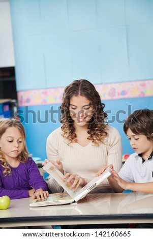 Beautiful young teacher and children reading book in classroom - stock photo