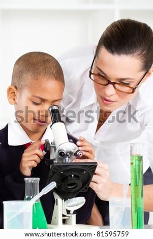 beautiful young teacher helping school boy in science class - stock photo
