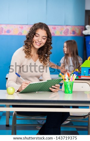 Beautiful young teacher writing in book with student playing in background at kindergarten - stock photo