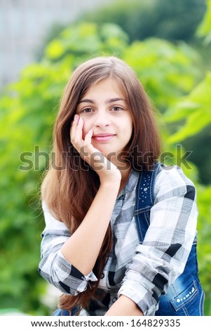 Beautiful young teenage girl in green jacket looking to copyspace outdoors  - stock photo