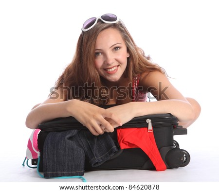 Beautiful young teenager school girl leaning on top of suitcase with big smile packing for her vacation. Clothes falling out of case onto floor. - stock photo