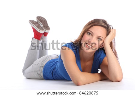 Beautiful young teenager school girl 16, with long brown hair wearing blue t-shirt and denim jeans, lying on the floor with a big smile. - stock photo