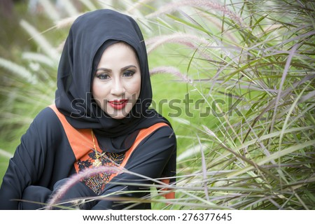 Beautiful Young Thai Muslim Woman with Abaya Dressed Outdoors. Enjoy Nature. Healthy Smiling Girl in Green Grass.