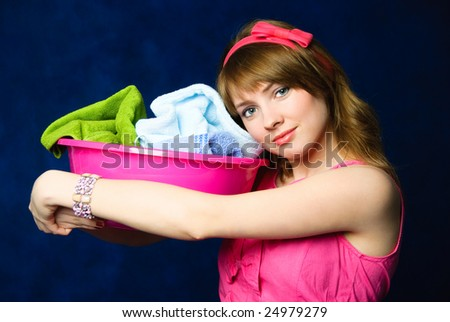 beautiful young tired housewife with a basin full of dirty clothes