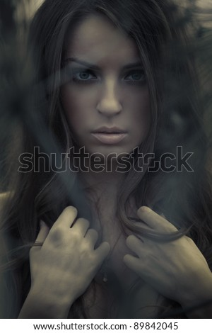Beautiful young topless woman posing outdoors. Dark mysterious artistic portrait. - stock photo