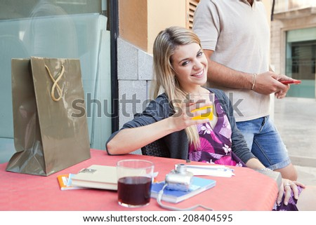 Beautiful young tourist couple sitting at a cafe bar terrace drinking refreshments with their shopping bags, visiting a destination city and using smartphone technology outdoors. Travel lifestyle. - stock photo