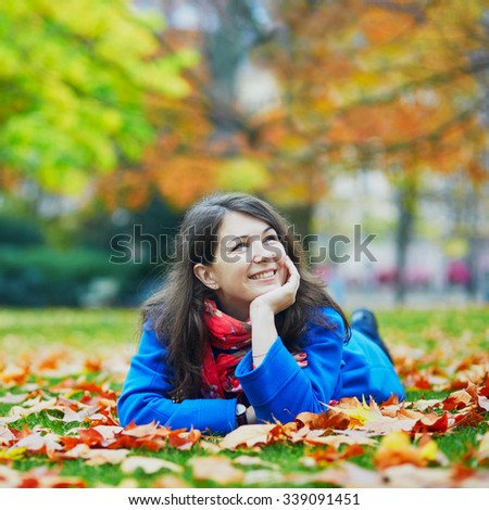 Beautiful young tourist in Paris on a fall day, laying on the ground in the Luxembourg garden with colorful autumn leaves - stock photo