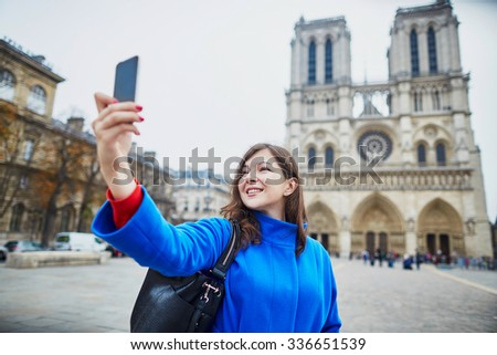 Beautiful young tourist in Paris on a fall day, making selfie with Notre-Dame cathedral - stock photo