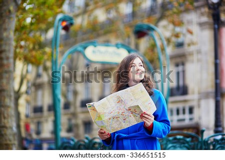 Beautiful young tourist in Paris on a fall day, using map and planning her itinerary - stock photo