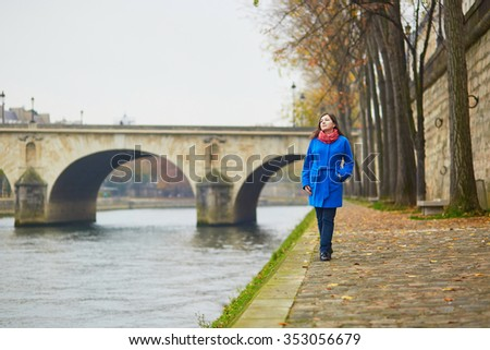 Beautiful young tourist in Paris on a fall day, walking near the river Seine - stock photo