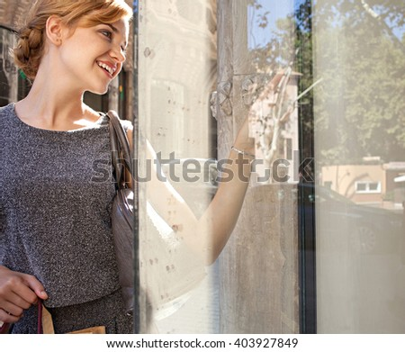 Beautiful young tourist woman carrying shopping bags in city with fashion stores, joyfully smiling and looking at shop windows, sunny outdoors. Consumer girl, exclusive expensive lifestyle exterior. - stock photo